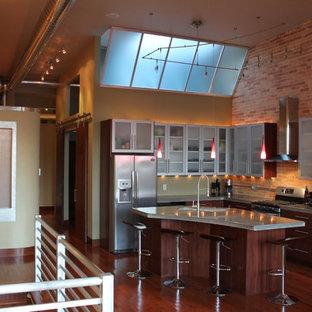 他の地域の中サイズのコンテンポラリースタイルのおしゃれなキッチン (アンダーカウンターシンク、ガラス扉のキャビネット、グレーのキャビネット、コンクリートカウンター、レンガのキッチンパネル、シルバーの調理設備の、無垢フローリング) の写真