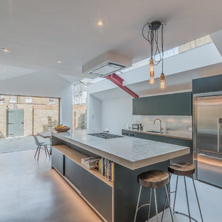 Inspiration for a medium sized urban galley open plan kitchen in London with a single-bowl sink, flat-panel cabinets, black cabinets, concrete worktops, metallic splashback, stainless steel appliances, concrete flooring and an island.