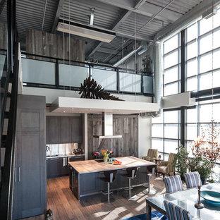 トロントの中サイズのインダストリアルスタイルのおしゃれなキッチン (ドロップインシンク、シェーカースタイル扉のキャビネット、茶色いキャビネット、大理石カウンター、白いキッチンパネル、シルバーの調理設備の、無垢フローリング) の写真