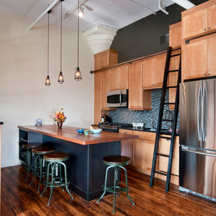 Industrial kitchen photos - Example of an urban single-wall kitchen design in Philadelphia with stainless steel appliances, wood countertops, shaker cabinets, medium tone wood cabinets and blue backsplash