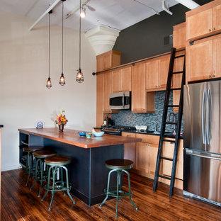 フィラデルフィアのインダストリアルスタイルのおしゃれなI型キッチン (シルバーの調理設備の、木材カウンター、シェーカースタイル扉のキャビネット、中間色木目調キャビネット、青いキッチンパネル) の写真