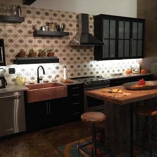 Идея дизайна: линейная кухня в стиле лофт с раковиной в стиле кантри, стеклянными фасадами, черными фасадами, мраморной столешницей, фартуком из цементной плитки, техникой из нержавеющей стали, бетонным полом, островом и розовой столешницей