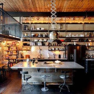 アトランタのインダストリアルスタイルのおしゃれなキッチン (アンダーカウンターシンク、ヴィンテージ仕上げキャビネット、コンクリートカウンター、白いキッチンパネル、サブウェイタイルのキッチンパネル、シルバーの調理設備の、コンクリートの床、黒い床、グレーのキッチンカウンター) の写真