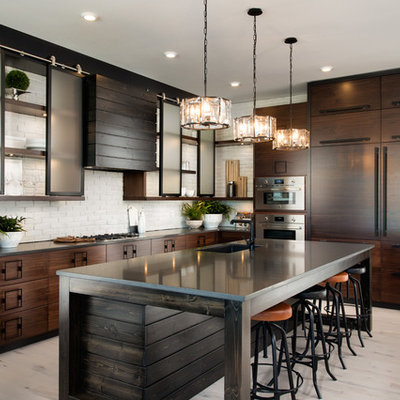 Eat-in kitchen - large industrial l-shaped light wood floor and beige floor eat-in kitchen idea in Other with an undermount sink, flat-panel cabinets, dark wood cabinets, white backsplash, brick backsplash, paneled appliances, an island and soapstone countertops