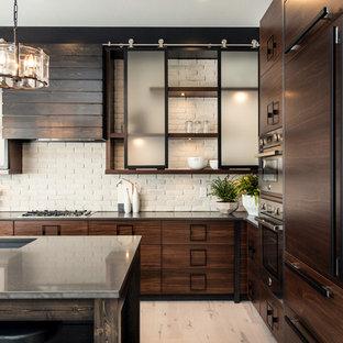 Foto på ett stort industriellt kök, med en undermonterad diskho, släta luckor, skåp i mörkt trä, bänkskiva i täljsten, vitt stänkskydd, stänkskydd i tegel, integrerade vitvaror, ljust trägolv, en köksö och beiget golv