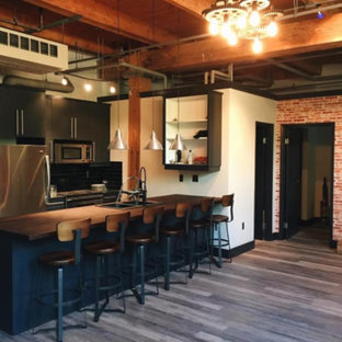 Design ideas for a mid-sized industrial galley open plan kitchen in Orange County with a double-bowl sink, flat-panel cabinets, black cabinets, wood benchtops, black splashback, subway tile splashback, stainless steel appliances, painted wood floors and with island.
