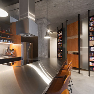 This is an example of a mid-sized industrial galley eat-in kitchen in Montreal with a drop-in sink, flat-panel cabinets, black cabinets, stainless steel benchtops, grey splashback, slate splashback, stainless steel appliances, slate floors, with island, grey floor and grey benchtop.