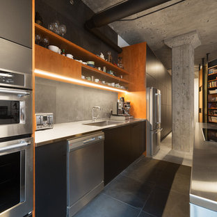 Design ideas for a mid-sized industrial galley eat-in kitchen in Montreal with a drop-in sink, flat-panel cabinets, black cabinets, stainless steel benchtops, grey splashback, slate splashback, stainless steel appliances, slate floors, with island, grey floor and grey benchtop.