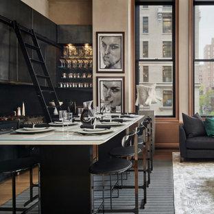 Kleine Moderne Wohnküche ohne Insel in L-Form mit Unterbauwaschbecken, flächenbündigen Schrankfronten, schwarzen Schränken, Granit-Arbeitsplatte, Küchenrückwand in Schwarz, Kalk-Rückwand, Elektrogeräten mit Frontblende, braunem Holzboden, beigem Boden und schwarzer Arbeitsplatte in New York