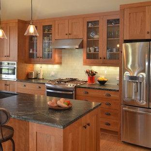 ワシントンD.C.の中サイズのおしゃれなキッチン (アンダーカウンターシンク、シェーカースタイル扉のキャビネット、中間色木目調キャビネット、ソープストーンカウンター、グレーのキッチンパネル、ガラスタイルのキッチンパネル、シルバーの調理設備、淡色無垢フローリング、茶色い床) の写真