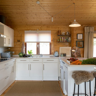 This is an example of a small rustic u-shaped open plan kitchen in Buckinghamshire with flat-panel cabinets, white cabinets, laminate countertops, white splashback, marble splashback, stainless steel appliances, light hardwood flooring, a breakfast bar, white worktops, a built-in sink and beige floors.