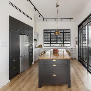 シカゴの中くらいのトランジショナルスタイルのおしゃれなキッチン (ダブルシンク、レイズドパネル扉のキャビネット、黒いキャビネット、珪岩カウンター、白いキッチンパネル、御影石のキッチンパネル、無垢フローリング、茶色い床、白いキッチンカウンター) の写真