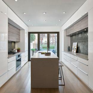 Неиссякаемый источник вдохновения для домашнего уюта: параллельная кухня в стиле модернизм с плоскими фасадами, столешницей из кварцевого композита, полом из бамбука и островом