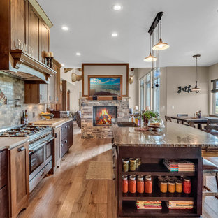 Mid-sized country galley kitchen in Denver with an undermount sink, dark wood cabinets, granite benchtops, stone tile splashback, stainless steel appliances, medium hardwood floors, with island, shaker cabinets, brown splashback, brown floor and brown benchtop.