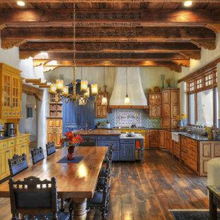 オースティンのサンタフェスタイルのおしゃれなキッチン (エプロンフロントシンク、レイズドパネル扉のキャビネット、中間色木目調キャビネット、青いキッチンパネル、濃色無垢フローリング) の写真