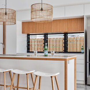 Inspiration for a beach style kitchen in Gold Coast - Tweed with a drop-in sink, flat-panel cabinets, medium wood cabinets, window splashback, stainless steel appliances, grey floor and white benchtop.