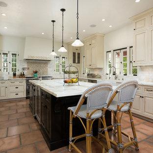 ロサンゼルスの地中海スタイルのおしゃれなキッチン (エプロンフロントシンク、レイズドパネル扉のキャビネット、ベージュのキャビネット、大理石カウンター、白いキッチンパネル、シルバーの調理設備、テラコッタタイルの床、サブウェイタイルのキッチンパネル) の写真