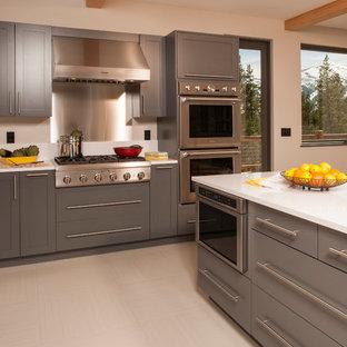 Immagine di una cucina design di medie dimensioni con lavello sottopiano, ante con riquadro incassato, ante grigie, top in quarzo composito, paraspruzzi giallo, elettrodomestici in acciaio inossidabile e pavimento in gres porcellanato