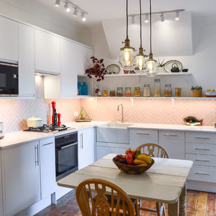 Photo of a contemporary l-shaped kitchen/diner in London with a belfast sink, raised-panel cabinets, white cabinets, pink splashback, integrated appliances, medium hardwood flooring, no island, brown floors and white worktops.
