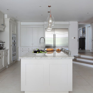 Photo of a traditional l-shaped kitchen in London with a submerged sink, shaker cabinets, white cabinets, grey splashback, stainless steel appliances, an island, beige floors and white worktops.