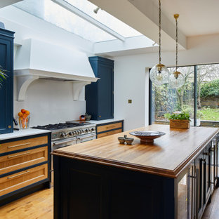 This is an example of a large traditional galley open plan kitchen in London with a belfast sink, shaker cabinets, blue cabinets, quartz worktops, grey splashback, stone slab splashback, stainless steel appliances, dark hardwood flooring, an island, brown floors and grey worktops.