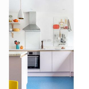 Ispirazione per una piccola cucina contemporanea con lavello a vasca singola, ante lisce, top alla veneziana, paraspruzzi multicolore, elettrodomestici da incasso, pavimento in laminato, isola, pavimento blu e top multicolore