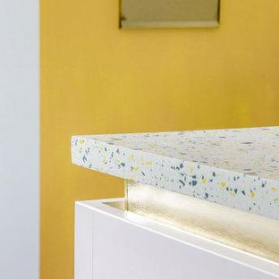 Foto di una piccola cucina minimal con lavello a vasca singola, ante lisce, top alla veneziana, paraspruzzi multicolore, elettrodomestici da incasso, pavimento in laminato, isola, pavimento blu e top multicolore