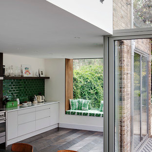 Eclectic kitchen in London with flat-panel cabinets, white cabinets, green splashback and subway tile splashback.