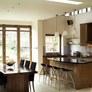 This is an example of a contemporary l-shaped open plan kitchen in London with shaker cabinets, medium wood cabinets, grey splashback, stainless steel appliances and an island.