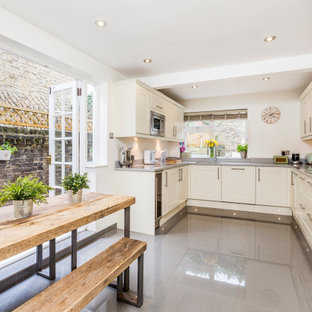 Photo of a traditional u-shaped kitchen/diner in London with a submerged sink, shaker cabinets, white cabinets, stainless steel appliances, no island, grey floors and grey worktops.