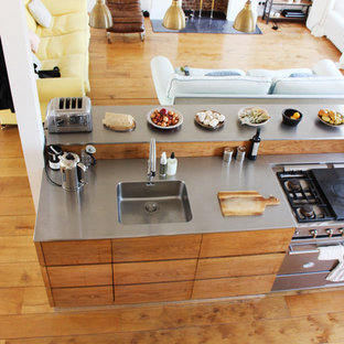 Large midcentury galley eat-in kitchen in London with a drop-in sink, flat-panel cabinets, medium wood cabinets, stainless steel benchtops, brown splashback, timber splashback, stainless steel appliances, medium hardwood floors, with island, brown floor and grey benchtop.