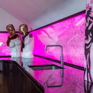На фото: маленькая п-образная кухня-гостиная в современном стиле с врезной раковиной, плоскими фасадами, темными деревянными фасадами, гранитной столешницей, разноцветным фартуком, фартуком из зеркальной плитки и черной техникой без острова