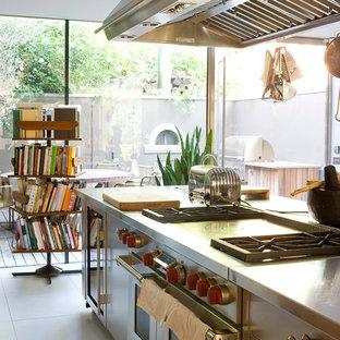 ロンドンのシャビーシック調のおしゃれなキッチン (ステンレスカウンター、フラットパネル扉のキャビネット、ステンレスキャビネット、シルバーの調理設備) の写真