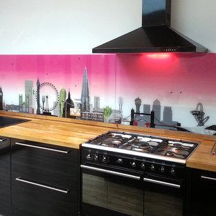 Неиссякаемый источник вдохновения для домашнего уюта: большая прямая кухня в стиле модернизм с обеденным столом, накладной раковиной, фасадами с выступающей филенкой, темными деревянными фасадами, деревянной столешницей, фартуком из стекла, черной техникой, полом из сланца, островом и разноцветным фартуком