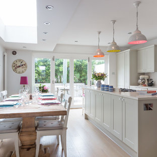 This is an example of a traditional kitchen in London with shaker cabinets, grey cabinets, white splashback, metro tiled splashback and light hardwood flooring.