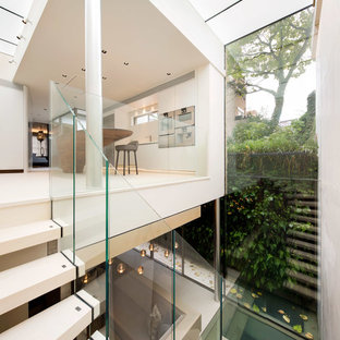 Modelo de cocina lineal, minimalista, grande, abierta, con fregadero encastrado, puertas de armario blancas, encimera de zinc, salpicadero blanco, electrodomésticos de acero inoxidable, suelo de terrazo, una isla y suelo blanco
