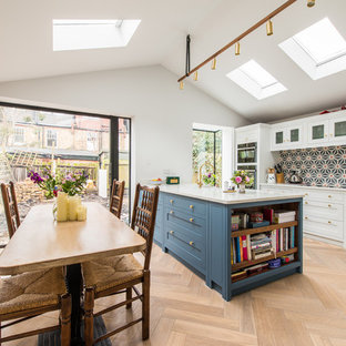 Photo of a classic galley kitchen/diner in Kent with shaker cabinets, blue cabinets, blue splashback, ceramic splashback, black appliances, light hardwood flooring, an island and white worktops.