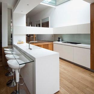 ロンドンのコンテンポラリースタイルのおしゃれなキッチン (ダブルシンク、フラットパネル扉のキャビネット、白いキャビネット、グレーのキッチンパネル、ガラス板のキッチンパネル、淡色無垢フローリング、白いキッチンカウンター) の写真