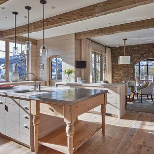 Modelo de cocina comedor en U, de estilo de casa de campo, grande, con fregadero sobremueble, armarios con paneles lisos, puertas de armario grises, encimera de zinc, suelo de madera en tonos medios y una isla