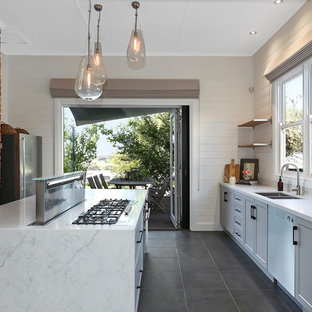 Inspiration for a transitional galley kitchen in Geelong with a double-bowl sink, recessed-panel cabinets, grey cabinets, white splashback, stainless steel appliances, with island, grey floor and white benchtop.