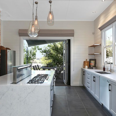 Example of a transitional galley gray floor kitchen design in Geelong with a double-bowl sink, recessed-panel cabinets, gray cabinets, white backsplash, stainless steel appliances, an island and white countertops