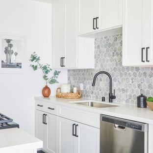 Foto di una piccola cucina parallela classica con lavello sottopiano, ante in stile shaker, ante bianche, paraspruzzi grigio, elettrodomestici in acciaio inossidabile e top bianco