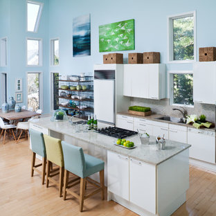 Inspiration for a large beach style galley eat-in kitchen in New York with flat-panel cabinets, white cabinets, light hardwood floors, an undermount sink, quartzite benchtops, white splashback, stone slab splashback, white appliances, with island, beige floor and white benchtop.