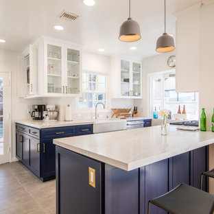 Mid-sized transitional u-shaped open plan kitchen in Los Angeles with a farmhouse sink, shaker cabinets, blue cabinets, stainless steel appliances, a peninsula, beige floor, beige benchtop, marble benchtops and porcelain floors.