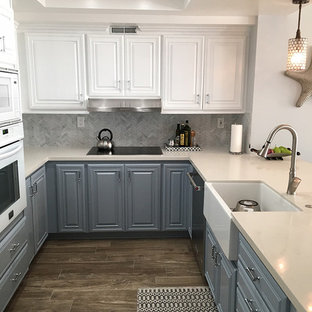 This is an example of a small transitional u-shaped eat-in kitchen in Los Angeles with a farmhouse sink, recessed-panel cabinets, blue cabinets, quartzite benchtops, white splashback, mosaic tile splashback, stainless steel appliances, porcelain floors and multi-coloured floor.
