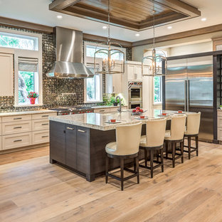 Design ideas for an expansive transitional u-shaped open plan kitchen in Other with a farmhouse sink, recessed-panel cabinets, white cabinets, granite benchtops, metallic splashback, metal splashback, stainless steel appliances, light hardwood floors, with island, beige floor and multi-coloured benchtop.