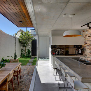 Photo of a mid-sized contemporary eat-in kitchen in Sydney with a drop-in sink, concrete benchtops, metal splashback, stainless steel appliances, concrete floors and with island.