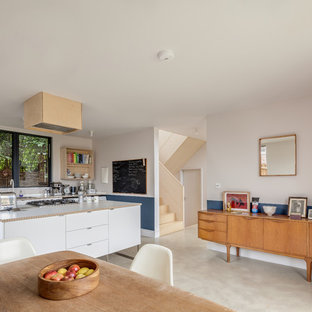 This is an example of a medium sized scandi single-wall kitchen/diner in Buckinghamshire with flat-panel cabinets, white cabinets, wood worktops, concrete flooring, an island, grey floors and beige worktops.