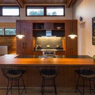 ボストンの中サイズのミッドセンチュリースタイルのおしゃれなキッチン (シングルシンク、フラットパネル扉のキャビネット、中間色木目調キャビネット、木材カウンター、黒いキッチンパネル、石タイルのキッチンパネル、パネルと同色の調理設備、無垢フローリング、茶色い床、黒いキッチンカウンター) の写真