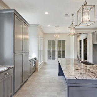 Large traditional galley eat-in kitchen in New Orleans with a farmhouse sink, shaker cabinets, grey cabinets, granite benchtops, white splashback, mosaic tile splashback, stainless steel appliances, ceramic floors and with island.